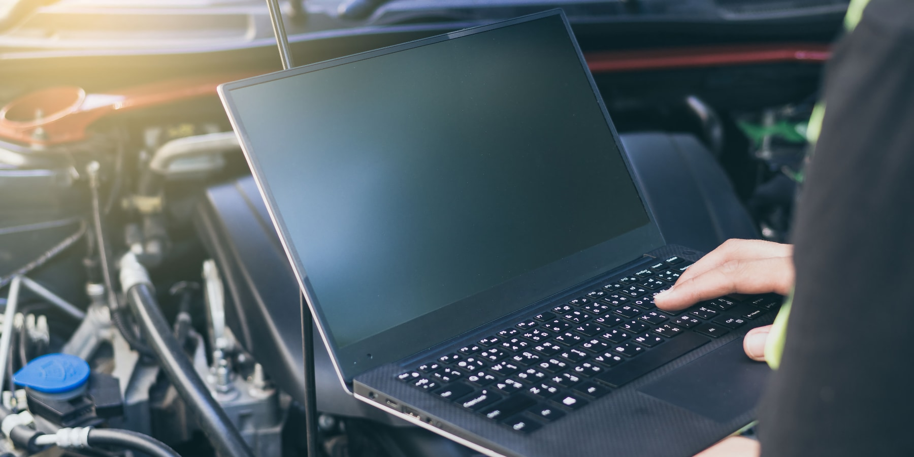 A car engine beeing assessed electronically via laptop.