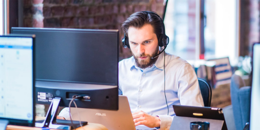 Man at desk in headset.