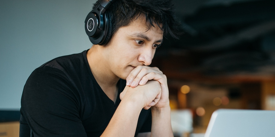 A man wearing headphones while concentrating in front of his laptop.