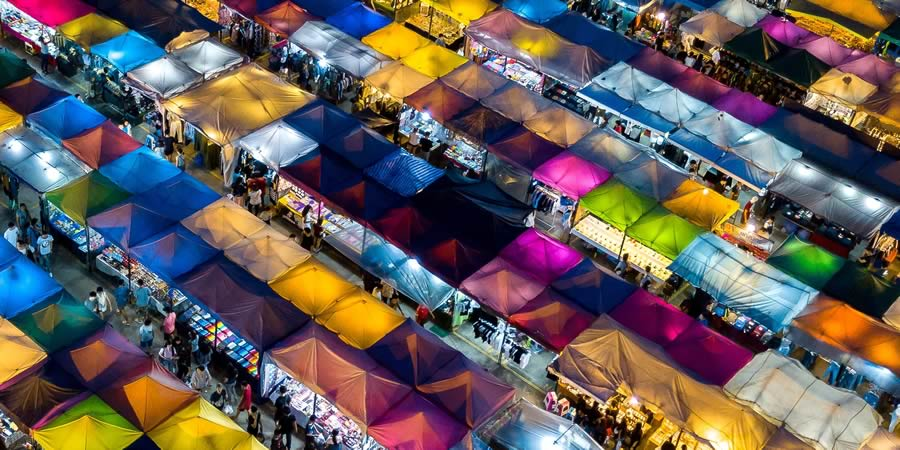 Covered marketplace, multi-coloured covers over dozens of stalls.