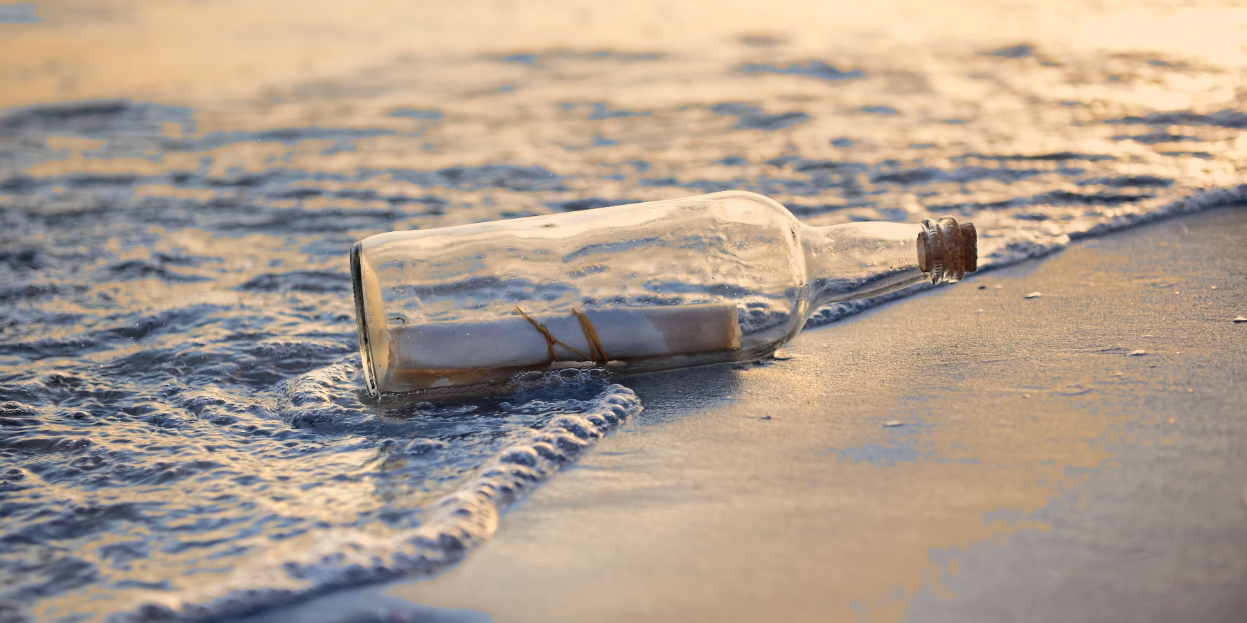 A message in a bottle on the beach, touched by the sea.