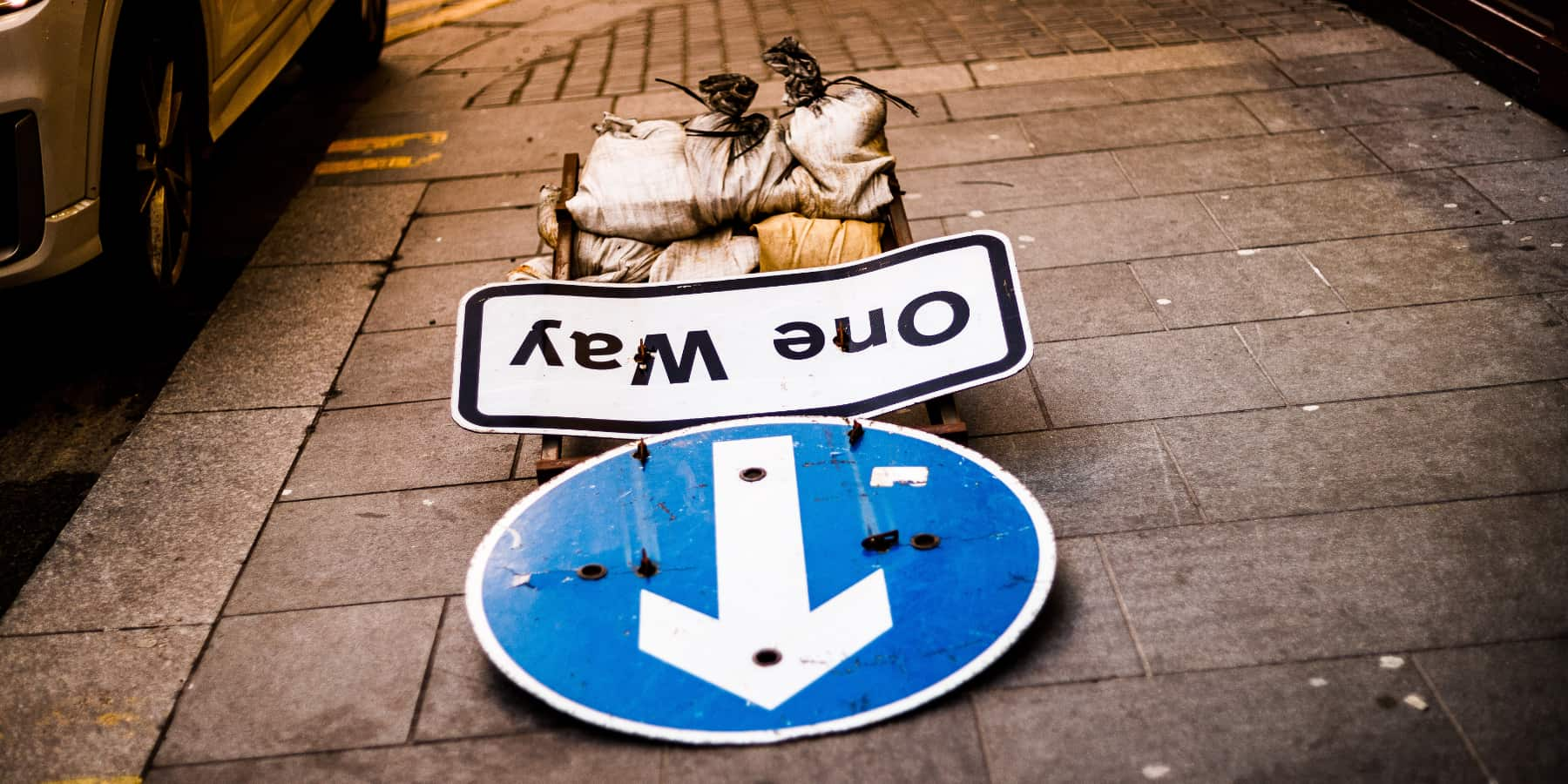 A one way sign, knocked down on the pavement.