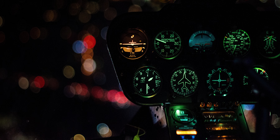 A plane's dashboard, lit up in the darkness.