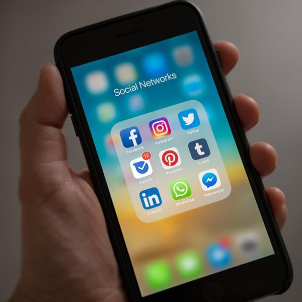 Phone showing apps, Facebook, Kaizala, WhatsApp, Twitter, etc.